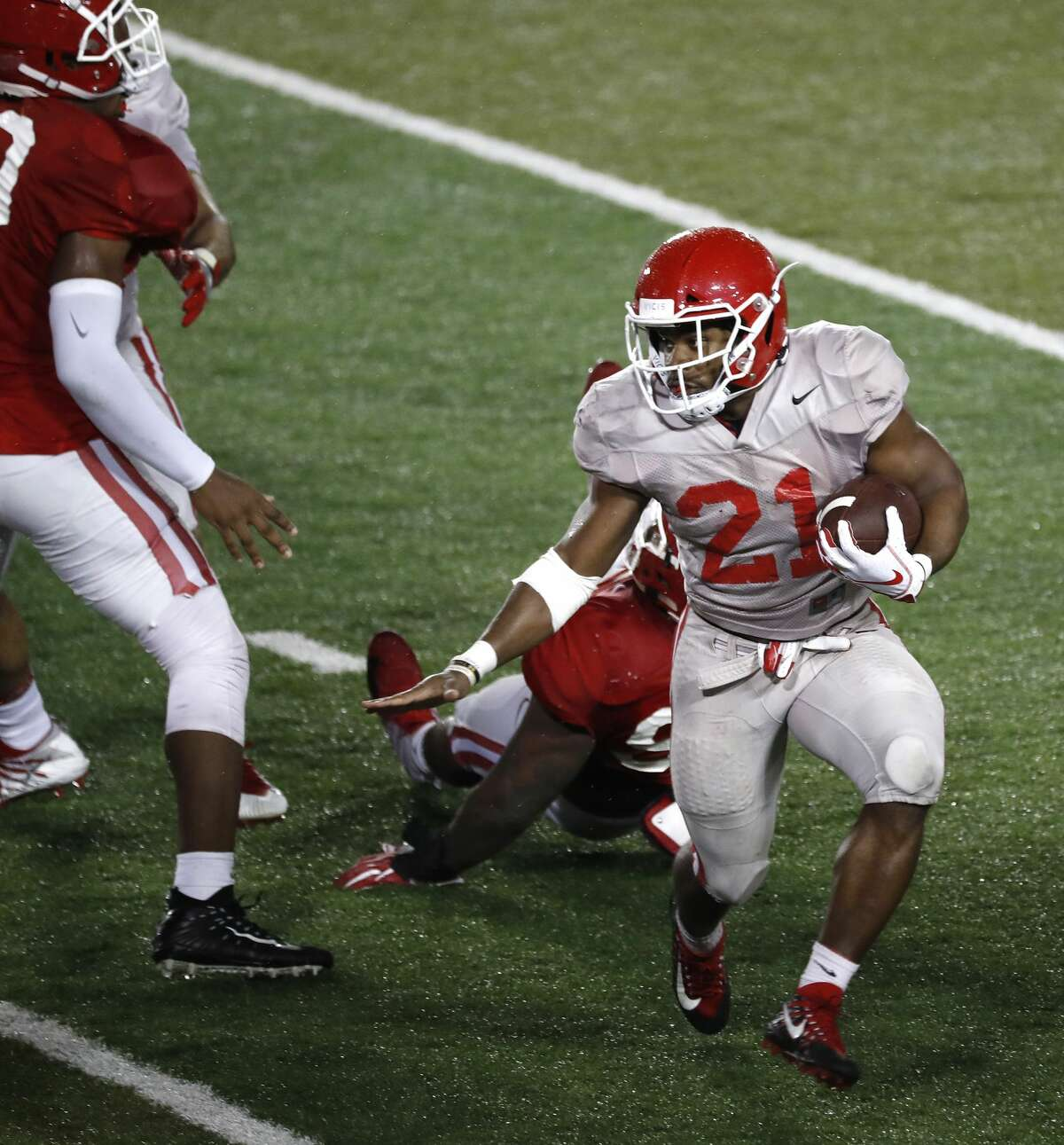 """Houston Cougars running back Patrick Carr (21) runs the ball during the University of Houston's """"Friday night lights"""" spring football practice, Friday, April 12, 2019, in Houston."""