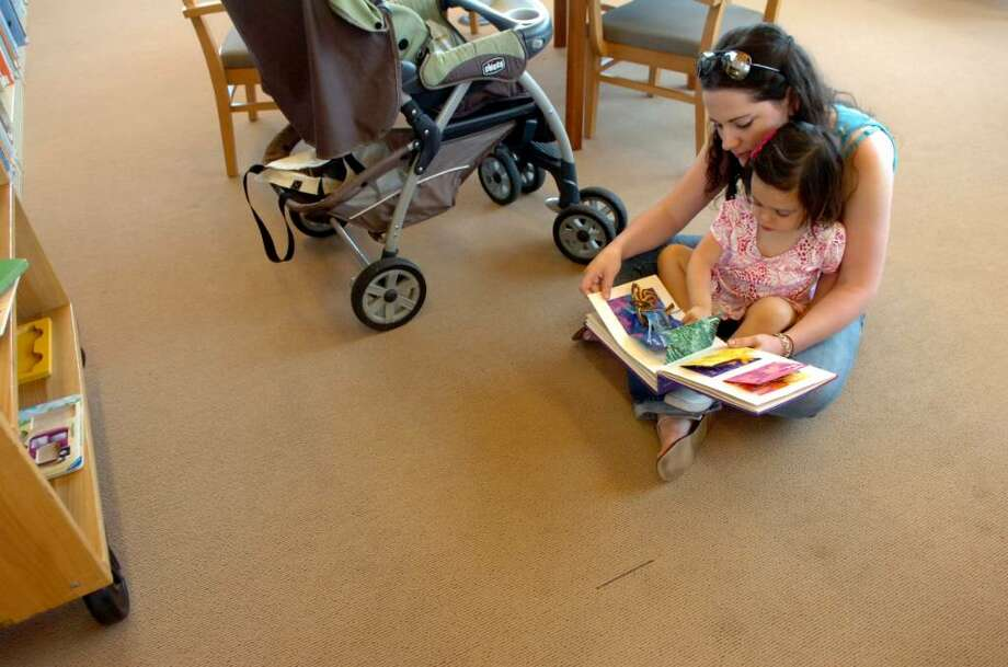 Lauren Cassel, of Wilton, sitting on the carpet, reads to her niece Audrey Carcache, 2, of Greenwich at the Byram Shubert Library, on Monday, July 26, 2010.  Although it was installed just over a year ago, the carpet at the Byram Shubert Library is already worn and frayed in areas and shows stains. The Building Committee discovered that the carpet installed at the Byram Shubert Library was not the carpet specified by the architect. The library will be closed from August 7-22 to install the new carpeting. Photo: Helen Neafsey / Greenwich Time