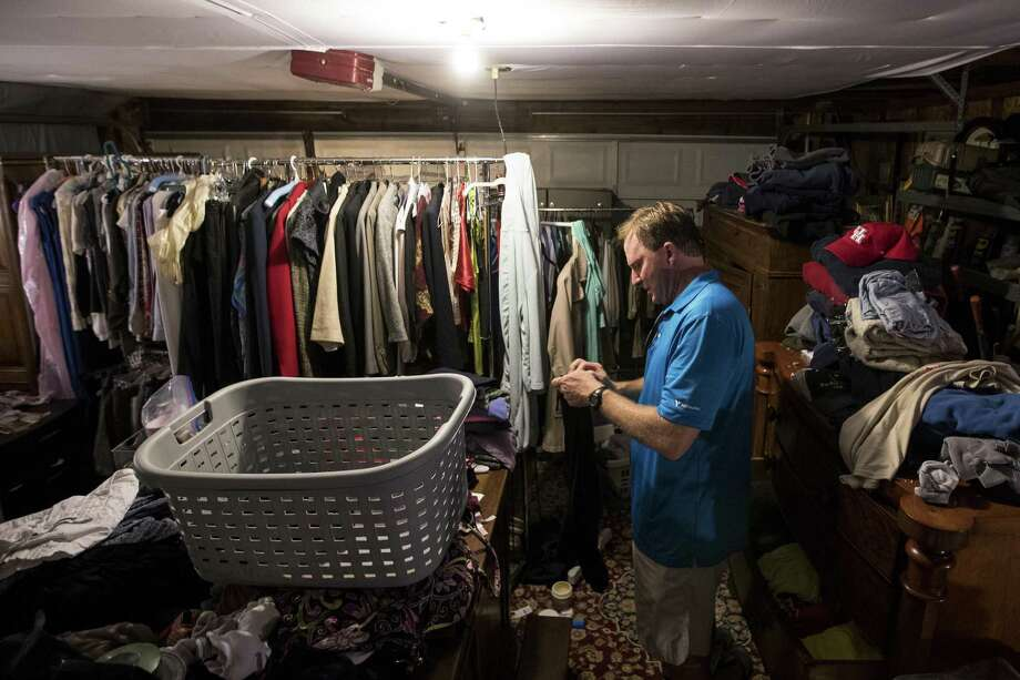 John Slaughter folds clothes in his garage as work continues on his flood-damaged home, on Thursday, June 28, 2018, in Kingwood. The Slaughters are in favor of a project to dredge a large sandbar in the San Jacinto River, to help alleviate flooding in Kingwood. They are still recovering from the floodwaters from Hurricane Harvey, where they had 52 inches of water inside their home. ( Brett Coomer / Houston Chronicle ) Photo: Brett Coomer, Staff Photographer / Houston Chronicle / © 2018 Houston Chronicle