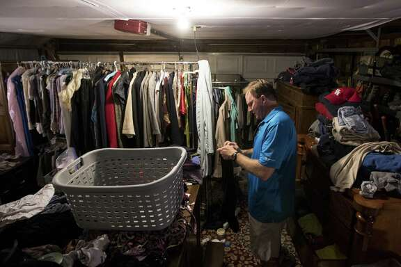 John Slaughter folds clothes in his garage as work continues on his flood-damaged home, on Thursday, June 28, 2018, in Kingwood. The Slaughters are in favor of a project to dredge a large sandbar in the San Jacinto River, to help alleviate flooding in Kingwood. They are still recovering from the floodwaters from Hurricane Harvey, where they had 52 inches of water inside their home. ( Brett Coomer / Houston Chronicle )