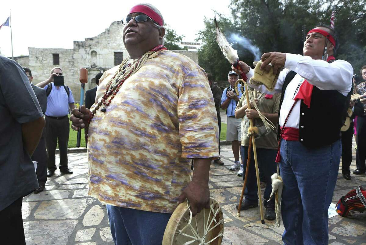 In this 2015 photo, Epifanio Hernandez, left, and Adrian Ramirez, descendants of Native Americans, give blessing to the four corners of the earth as city leaders celebrate the announcement of the San Antonio's Spanish missions winning World Heritage Site status in front of The Alamo, Two competing requests to designate the Alamo in San Antonio as a Historic Texas Cemetery could change how the mission is remembered. The Texas General Land Office wants to have the Alamo church listed as a historic Texas cemetery, citing the names of three people buried there nearly a century before the 1836 battle. Another proposal from Native American groups seeks a much larger area be designated a cemetery at the revered site. (Bob Owen/The San Antonio Express-News via AP)