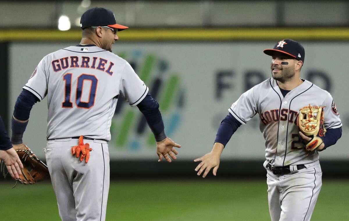 Houston Astros' Jose Altuve, right, greets Yuli Gurriel (10) after the Astros defeated the Seattle Mariners 10-6 in a baseball game, Friday, April 12, 2019, in Seattle. Both Altuve and Gurriel hit grand slams in the game. (AP Photo/Ted S. Warren)