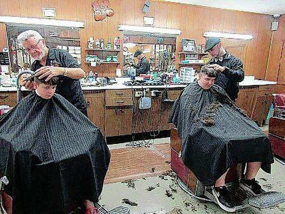 John Bargar, owner of the Colonial Barber Shop, and his grandson, Jake Gill, give haircuts to Jeffrey Wood and Adam Spradley in Pekin. Photo: Mike Kramer | Pekin Times (AP)