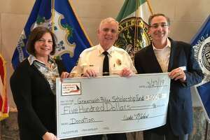 America's Boating Club of Greenwich presents the Greenwich Police Department with a check to benefit the GPD's Scholarship Fund. Vicki Malara, left, and Andy Cummings, right, with Chief of Police James Heavey, whose two children have completed the club's safe boating classes.