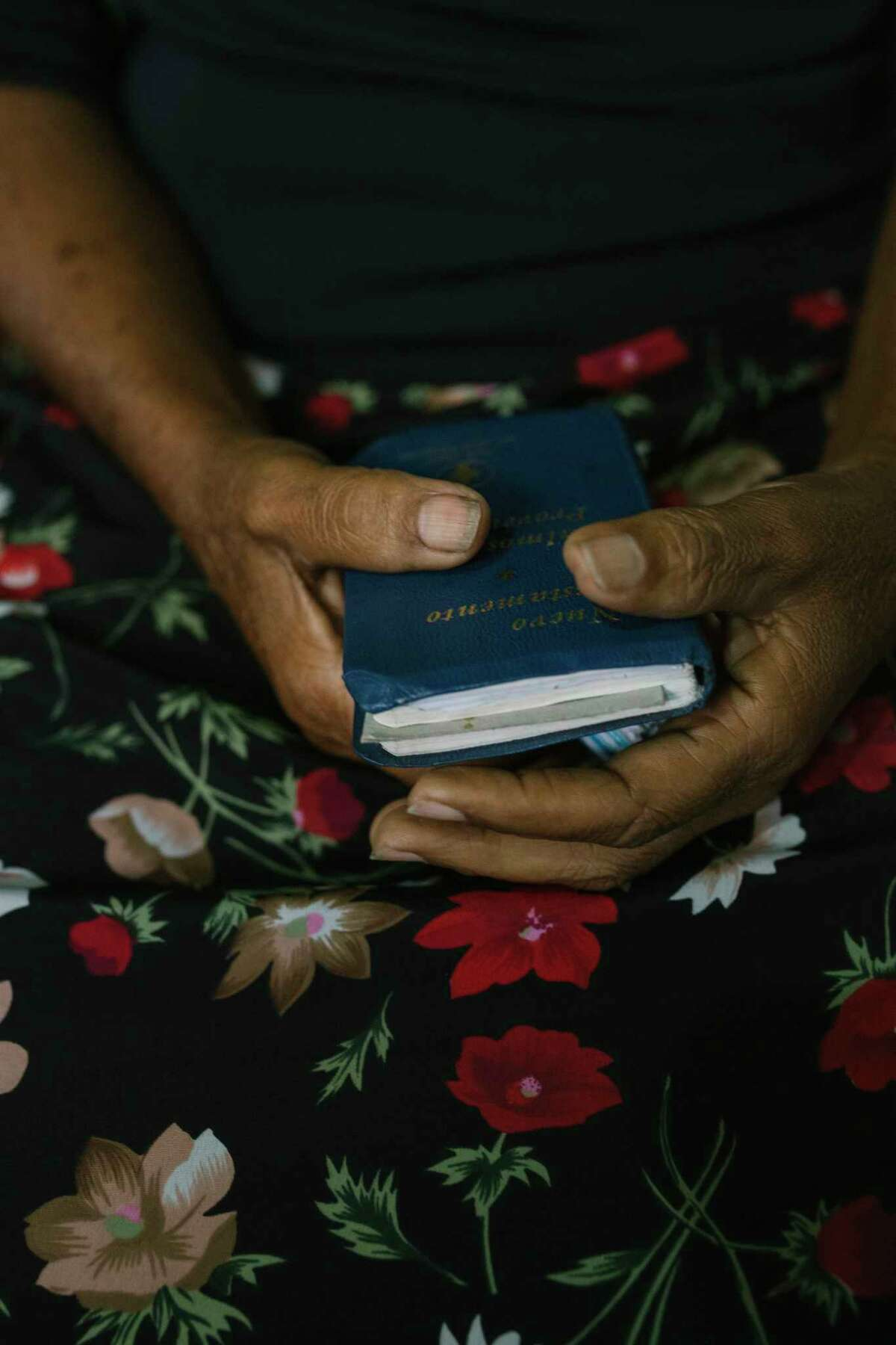 Mary Mendoza holds the New Testament as she waits for a service at an evangelical Christian church in the Caracas slum of Petare.