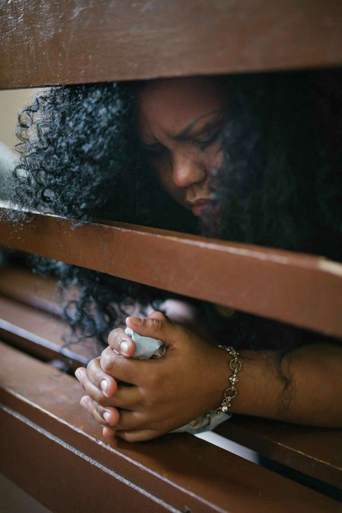 Leidy Villegas, 35, prays before the service begins.
