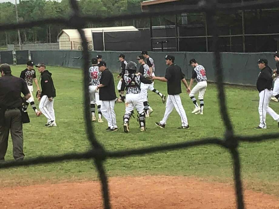 The Hargrave baseball coaches and players congratulate each other while walking off the field after a 16-4 win over Shepherd on April 12 in Huffman Photo: Elliott Lapin / Staff Photo