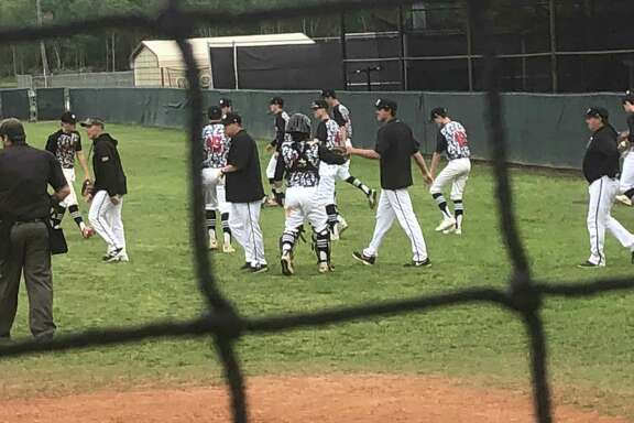 The Hargrave baseball coaches and players congratulate each other while walking off the field after a 16-4 win over Shepherd on April 12 in Huffman