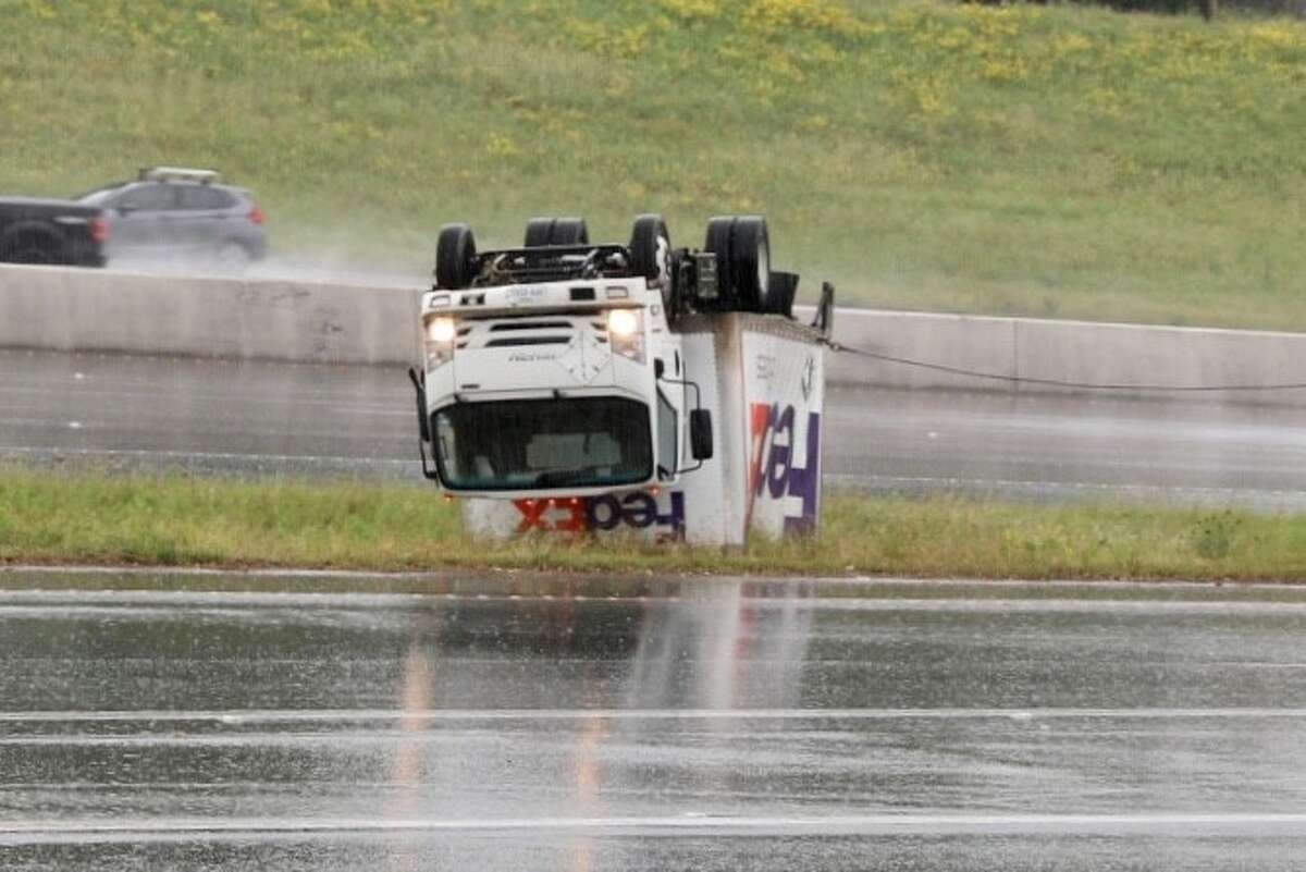 A FedEx delivery truck is seen overturned on the median on U.S. 281 and Nacoma Drive after heavy thunderstorms moved into the area Saturday morning April 13, 2019.