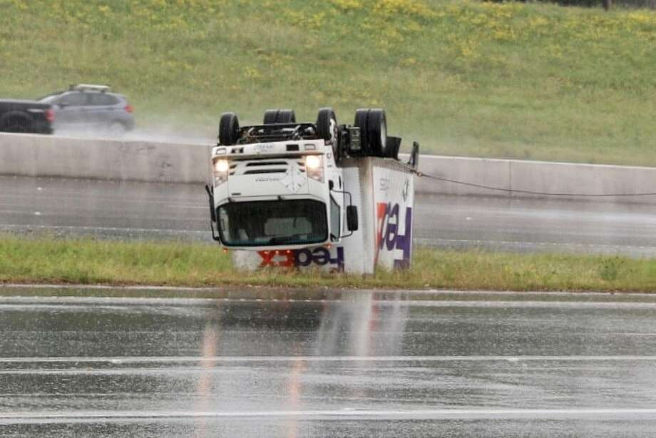 A FedEx delivery truck is seen overturned on the median on U.S. 281 and Nacoma Drive after heavy thunderstorms moved into the area Saturday morning April 13, 2019. Photo: Marco Garza For The Express-News