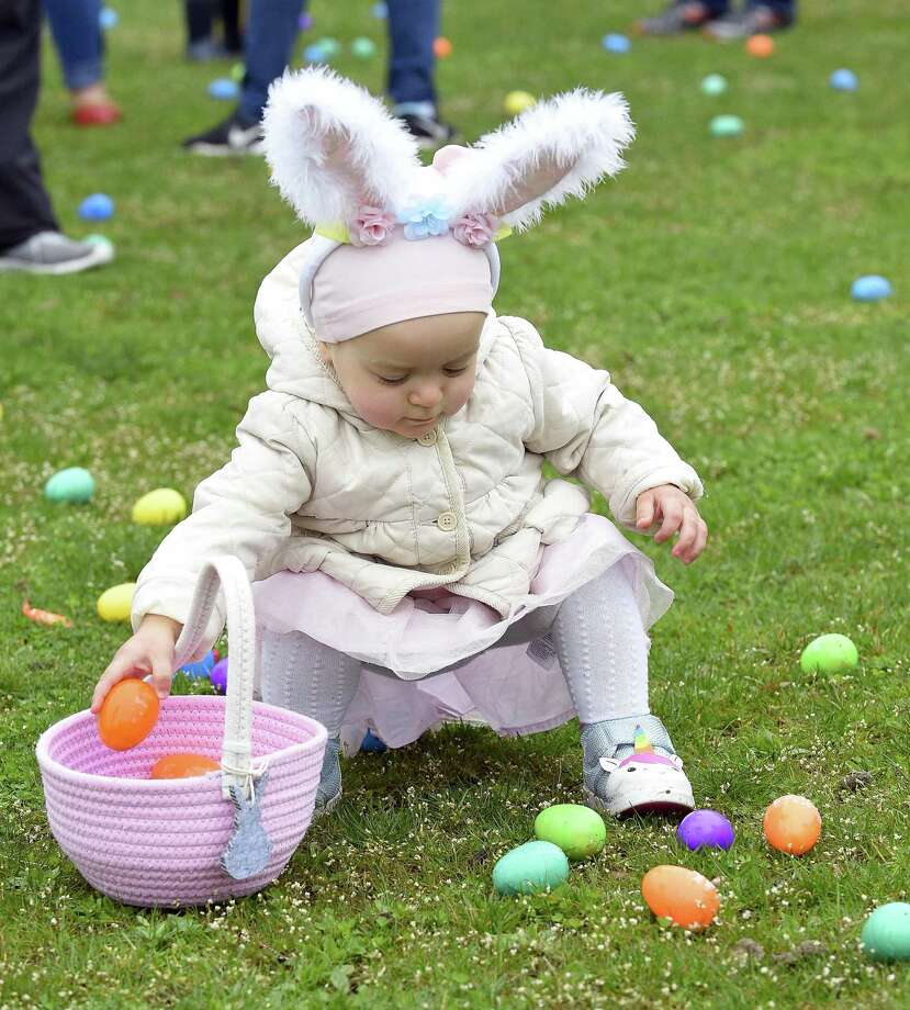 Solomia Nedria gathers eggs during the Big Egg Hunt at Roger Sherman Baldwin Park Saturday. The event, hosted by Greenwich's Harvest Time Church, featured a 20,000-egg patch for the children as well as games, face painting, balloon animals and prizes. Photo: Matthew Brown / Hearst Connecticut Media / Stamford Advocate