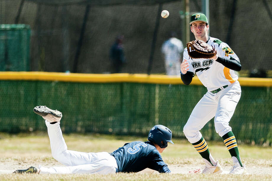 Dow's Jacob Stone catches the ball while a runner slides back into first base in a game against Petoskey during the Snowflake Classic on Saturday, April 13, 2019 at H. H. Dow High School. (Katy Kildee/kkildee@mdn.net) Photo: (Katy Kildee/kkildee@mdn.net)