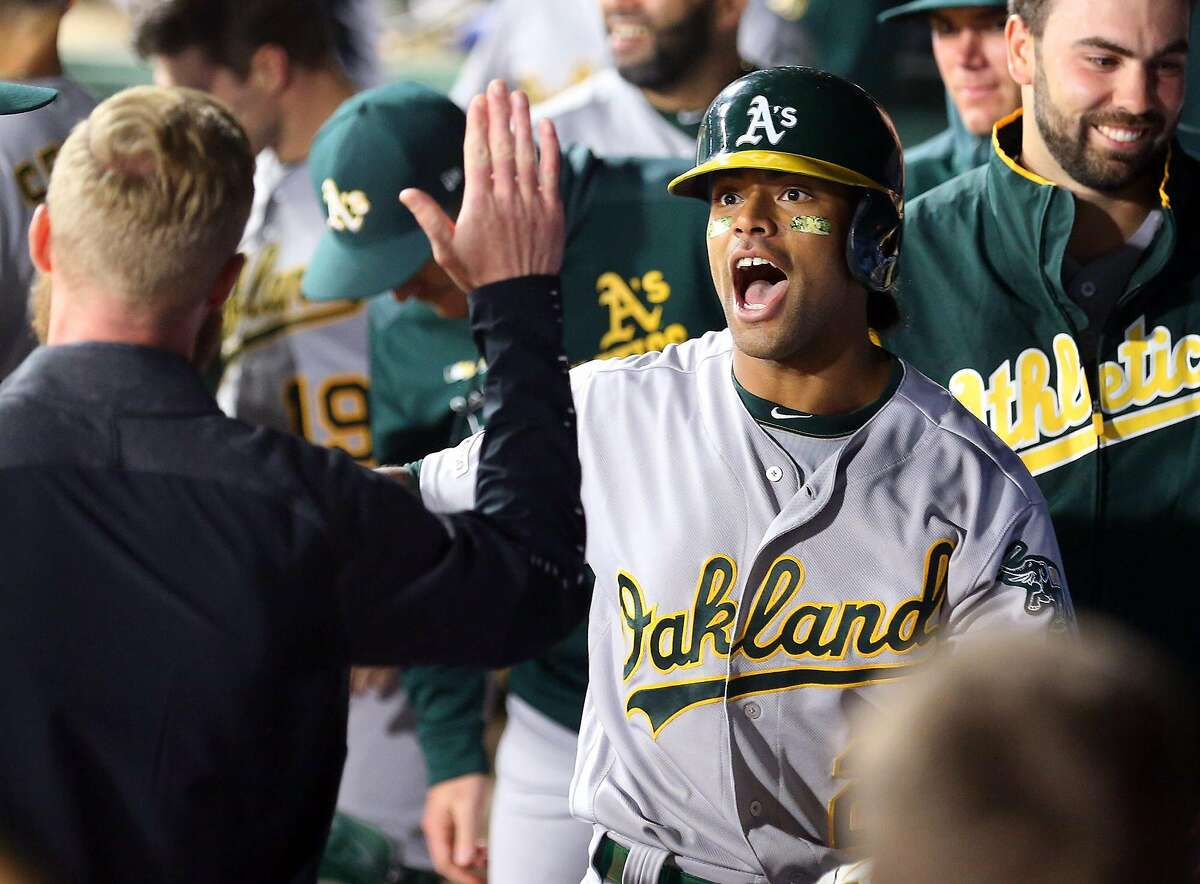 The Oakland Athletics' Khris Davis celebrates in the dugout after a solo home run in the eighth inning to take the lead against the Texas Rangers on Friday, April 12, 2019, at Globe Life Park in Arlington, Texas. The A's won, 8-6. (Richard W. Rodriguez/Fort Worth Star-Telegram/TNS)