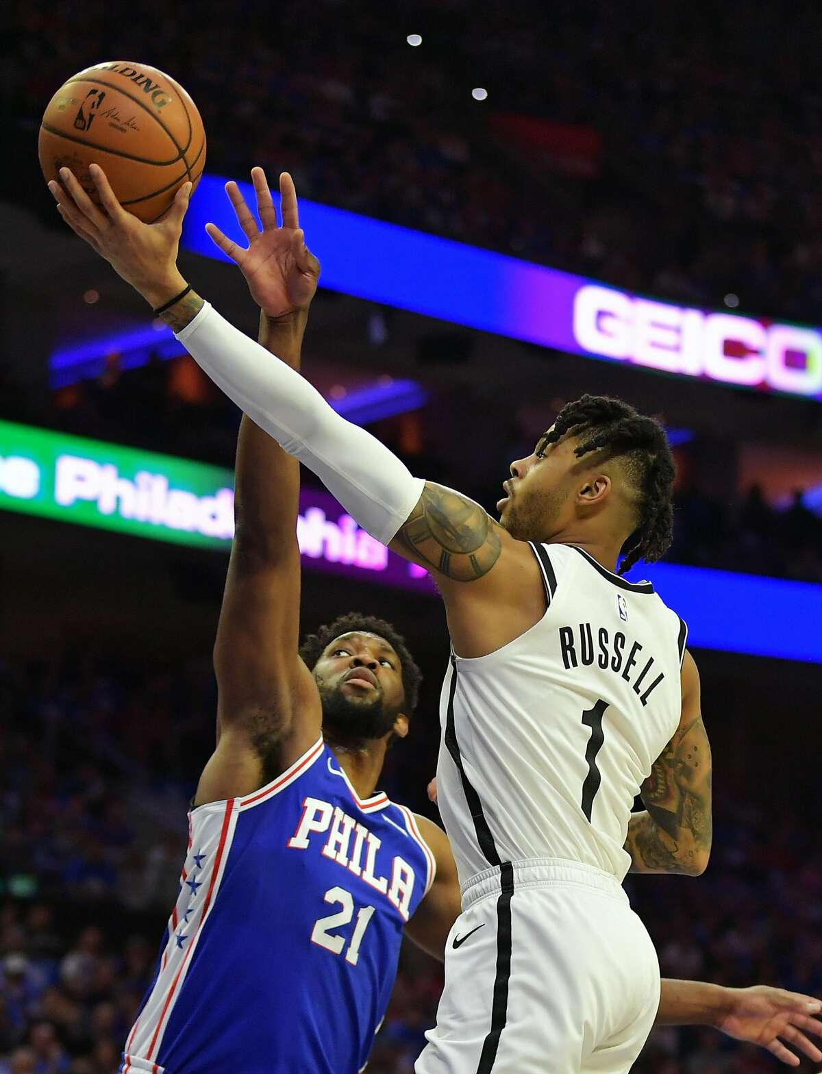PHILADELPHIA, PA - APRIL 13: D'Angelo Russell #1 of the Brooklyn Nets lays up a shot past Joel Embiid #21 of the Philadelphia 76ers in the first half during Game One of the first round of the 2019 NBA Playoff at Wells Fargo Center on April 13, 2019 in Philadelphia, Pennsylvania. NOTE TO USER: User expressly acknowledges and agrees that, by downloading and or using this photograph, User is consenting to the terms and conditions of the Getty Images License Agreement. (Photo by Drew Hallowell/Getty Images)