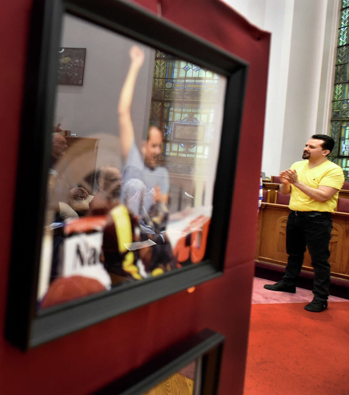 New Haven, Connecticut - Saturday, April 13, 2019: Nelson Pinos, an undocumented immigrant from Ecuador facing deportation, with his 500th day in sanctuary Saturday at the First and Summerfield Church in New Haven listens to a speaker during the opening of a photographic exhibition fundraising event Saturday evening for him and his family at the church.The photo exhibit documents Pinos, in sanctuary in New Haven since November 30, 2017, and Sujitno Sajuti, in sanctuary in Meriden since October 10. 2017. Pinos, a resident of New Haven, has lived in the U.S. since 1992. He is married and the father of three American citizen children