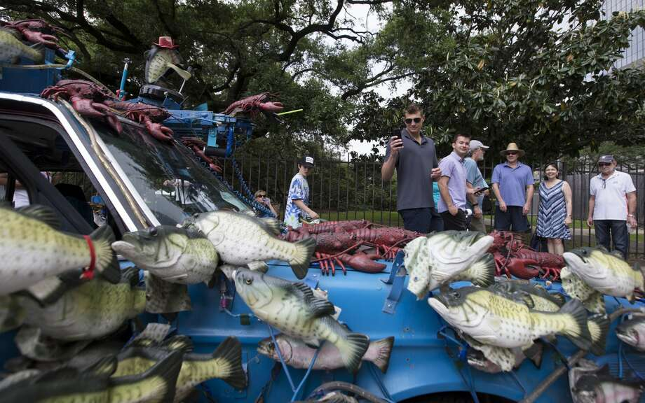"People stop to look and take photographs of the ""Billy the Big Mouth Bass"" art car at the 32nd  Annual Houston Art Car Parade on Saturday, April 13, 2019, in downtown Houston. Photo: Yi-Chin Lee/Staff Photographer"