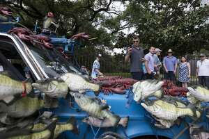 "People stop to look and take photographs of the ""Billy the Big Mouth Bass"" art car at the 32nd  Annual Houston Art Car Parade on Saturday, April 13, 2019, in downtown Houston."