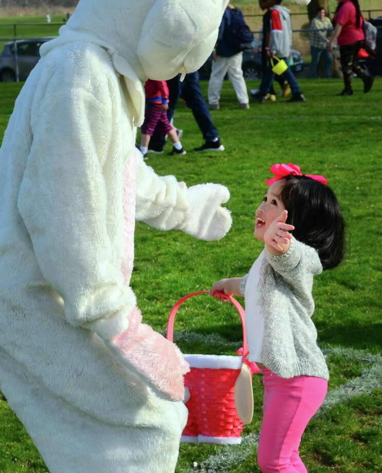 Lauren Caroline Lim, 4, of East Haven, greets the Easter bunny during the Annual Children's Easter Egg Scramble at the South Pine Creek soccer field in Fairfield, Conn., on Saturday Apr. 13, 2019. New this year in addition to the scramble, there was a Family Fun Zone, music, food trucks, a bounce house & giant slide, an obstacle course sponsored by BOOST, arts & crafts sponsored by AR Workshop and much more. There was also an inaugural Adult Sundown Easter Egg Hunt with great raffle prizes. Photo: Christian Abraham / Hearst Connecticut Media / Connecticut Post