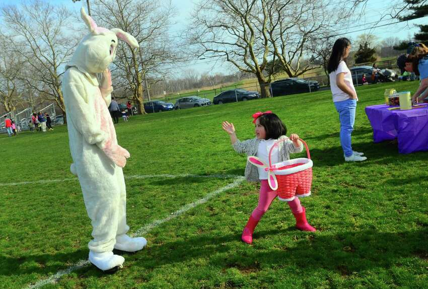 Lauren Caroline Lim, 4, of East Haven, waves goodbye to the Easter bunny during the Annual Children's Easter Egg Scramble at the South Pine Creek soccer field in Fairfield, Conn., on Saturday Apr. 13, 2019. New this year in addition to the scramble, there was a Family Fun Zone, music, food trucks, a bounce house & giant slide, an obstacle course sponsored by BOOST, arts & crafts sponsored by AR Workshop and much more. There was also an inaugural Adult Sundown Easter Egg Hunt with great raffle prizes.