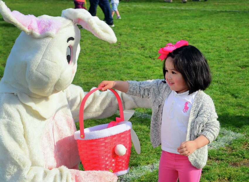 Lauren Caroline Lim, 4, of East Haven, greets the Easter bunny during the Annual Children's Easter Egg Scramble at the South Pine Creek soccer field in Fairfield, Conn., on Saturday Apr. 13, 2019. New this year in addition to the scramble, there was a Family Fun Zone, music, food trucks, a bounce house & giant slide, an obstacle course sponsored by BOOST, arts & crafts sponsored by AR Workshop and much more. There was also an inaugural Adult Sundown Easter Egg Hunt with great raffle prizes.