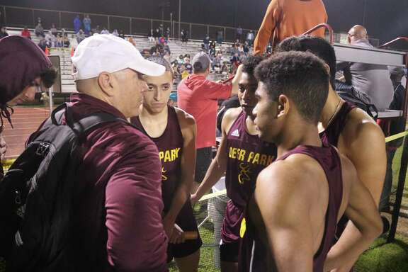 Deer Park coach P.J. Graham huddles with one of his relay squads earlier this season. His 4 by 200 squad clinched an Area meet berth by placing third at district, thanks to the time of 1:30.94.