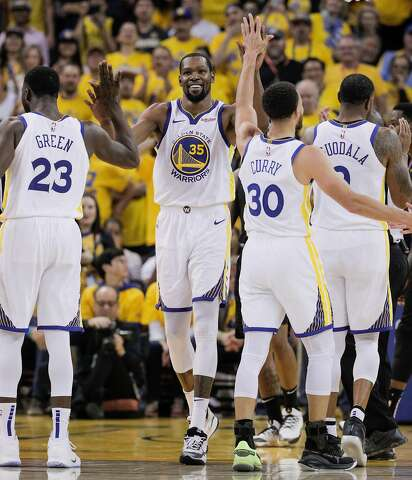 0fdcfabf6e23 Golden State Warriors Kevin Durant gets high fives from Draymond Green and  Stephen Curry after having