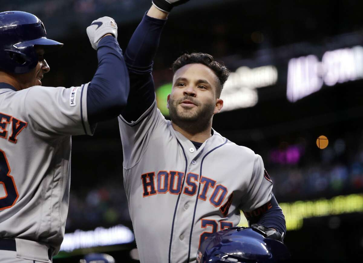 Houston Astros' Jose Altuve, right, is congratulated by Michael Brantley after Altuve hit a solo home run against the Seattle Mariners in the fifth inning of a baseball game Saturday, April 13, 2019, in Seattle. (AP Photo/Elaine Thompson)