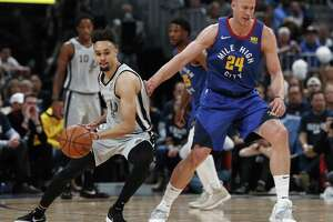 San Antonio Spurs guard Derrick White, left, pulls in a loose ball as Denver Nuggets forward Mason Plumlee defends in the second half of Game 1 of an NBA first-round basketball playoff series, Saturday, April 13, 2019, in Denver. The Spurs won 101-96. (AP Photo/David Zalubowski)