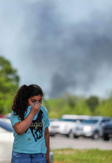 A little girl covers her nose as she and her family came to pick up a family member from the Crosby Kindergarten Center as the plume from the KMCO fire, billowed in the backround, Tuesday, April 2, 2019, in Crosby.