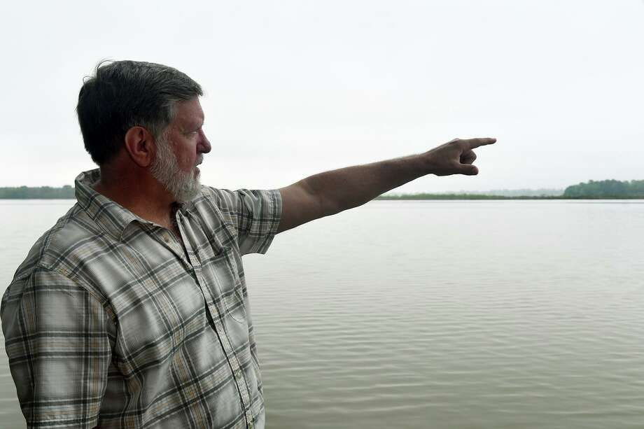Tim Garfield, a retired Exxon geologist who lives in Foster Mills Village in Kingwood, points to the island on the lake near Kings Point Trail on April 4, 2019. Photo: Jerry Baker, Houston Chronicle / Contributor / Houston Chronicle