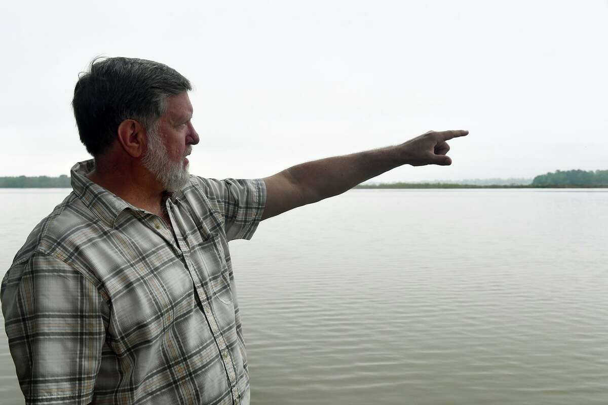 Tim Garfield, a retired Exxon geologist and a resident of Foster Mills Village in Kingwood, points to the island on the lake near Kings Point Trail on April 4, 2019.
