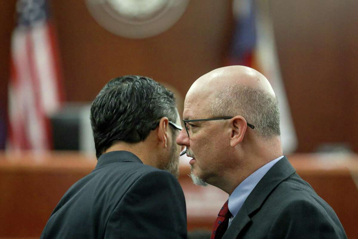 John Brewer, right, a prosecutor with the Harris County District Attorney's office, talks with Rick DeToto, a defense attorney for Antonio Armstrong, Jr., during Armstrong's capital murder trial on Tuesday, April 9, 2019, in Houston.