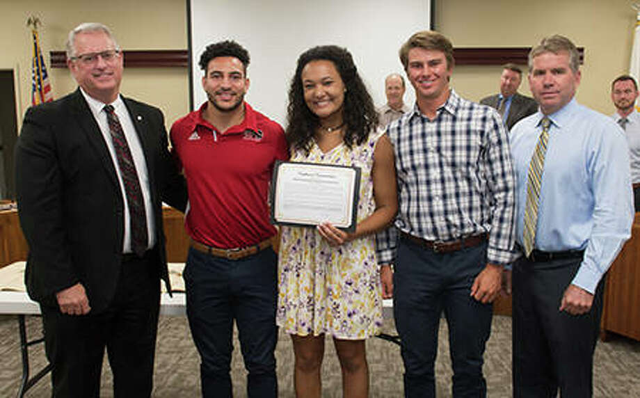 SIUE director of athletics Brad Hewitt, left, and Edwardsville mayor Hal Patton, right, presented NCAA All-American long jumper Julian Harvey (track and field), outside hitter Madison McKinley (volleyball) and catcher Brock Weimer (baseball) with certificates of commendation at a 2018 city council meeting to honor the Cougars' consistent academic excellence and community service. Harvey and Weimer are Edwardsville High School graduates. Hewitt is retiring effective June 30. Photo: For The Intelligencer