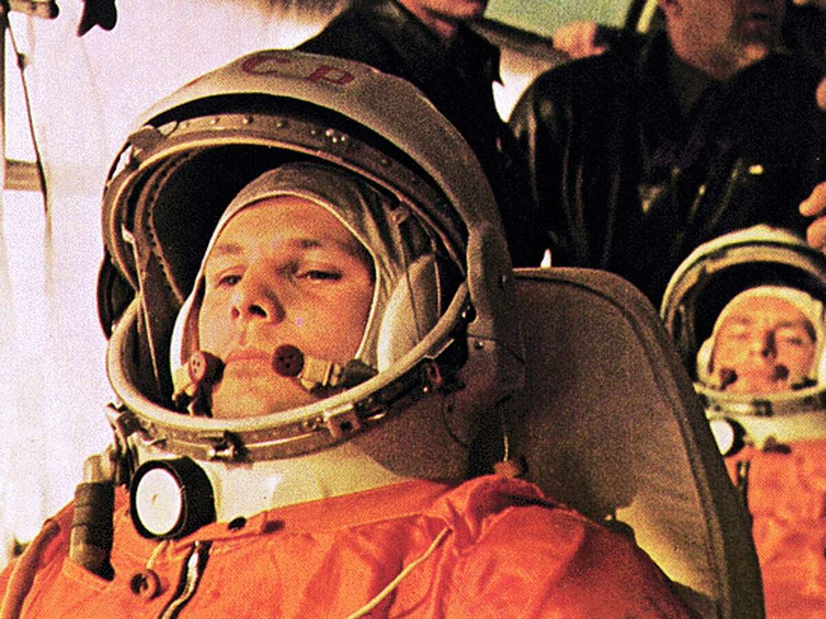 In this image Yuri Gagarin, pilot of the Vostok 1, is on the bus on the way to the launch. The cosmonaut behind Gagarin is German Titov, the back-up pilot who became pilot of Vostok 2.