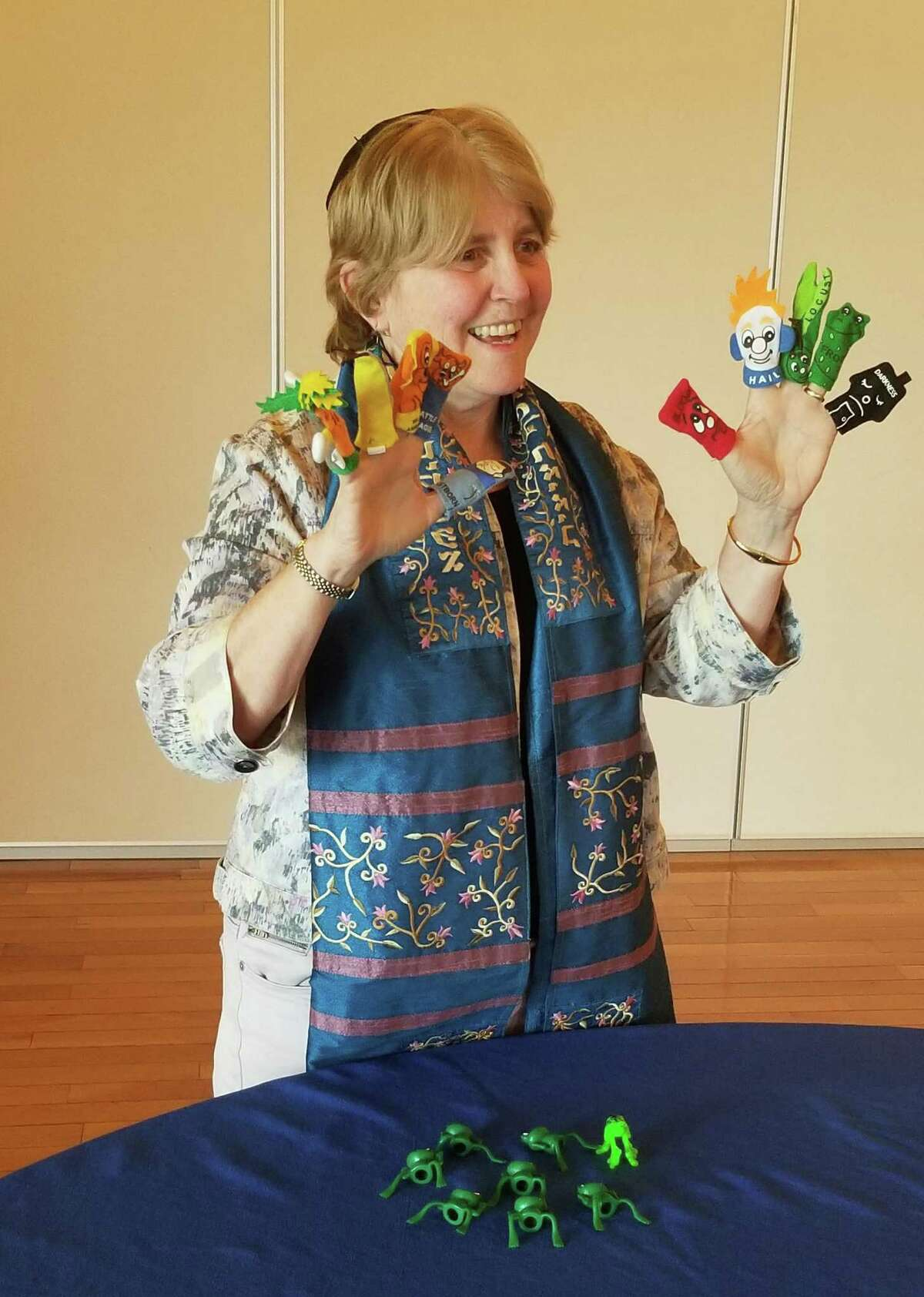 Passover celebrates freedom. Using finger puppets to represent the ten plagues, which are part of the story, can help bring it alive for children, says Rabbi Laurie Gold. Plastic frogs (on the table) can help, too. Gold is the rabbi at Temple Beth Elohim in Brewster, New York, just over the Connecticut border.