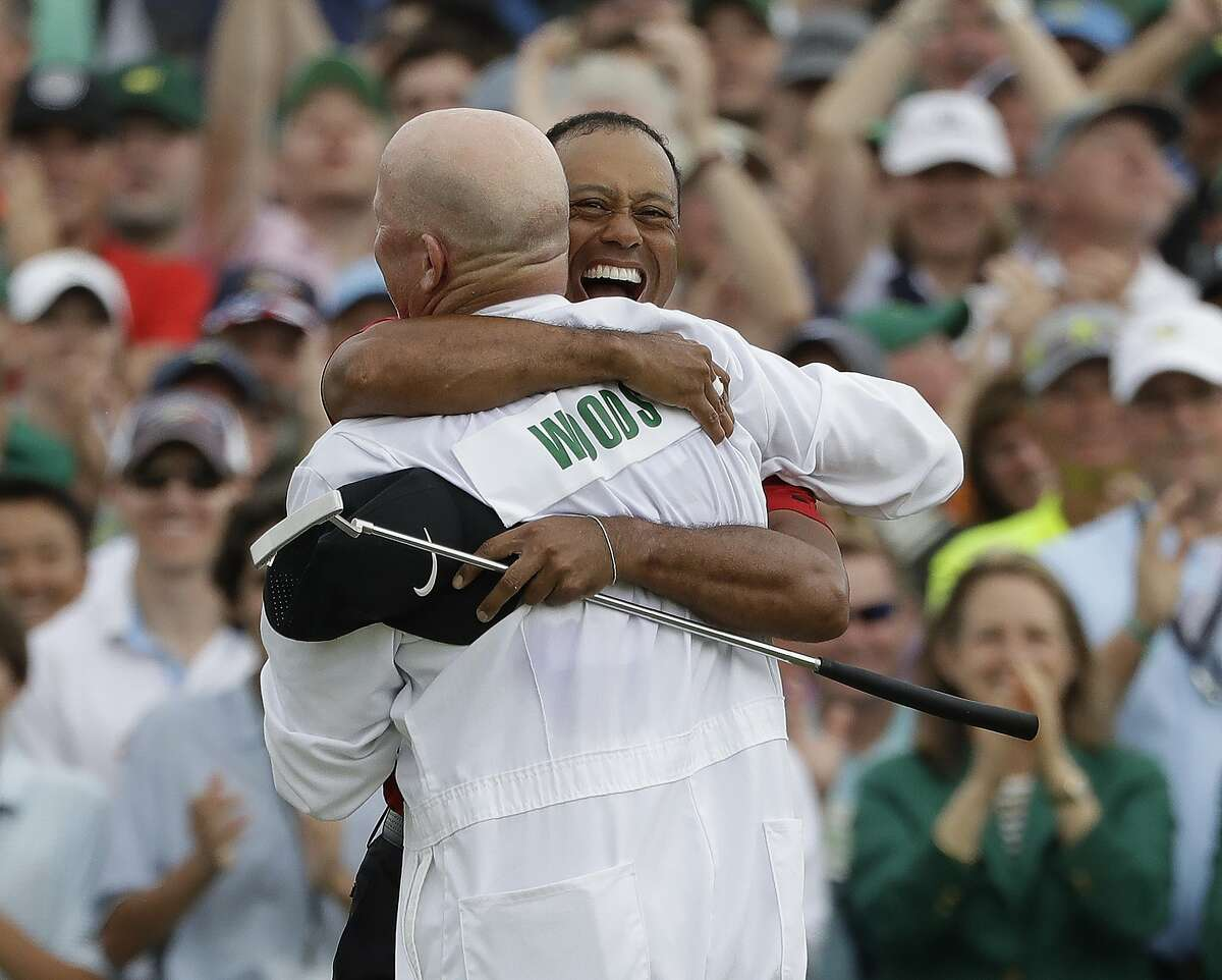 Tiger Woods reacts with his caddie Joe LaCava as he wins the Masters golf tournament Sunday, April 14, 2019, in Augusta, Ga. (AP Photo/Marcio Jose Sanchez)