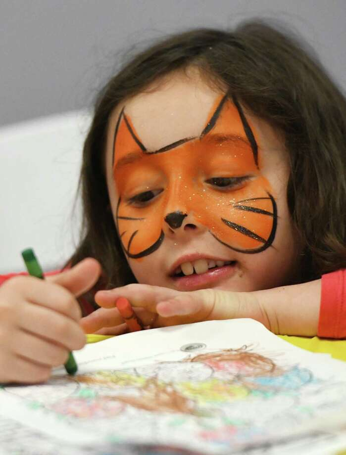 Cos Cob's Amanda Curtin, 6, has her face painted like a tiger as she colors at the Bunny Hop children's event at Chelsea Piers in Stamford, Conn. Sunday, April 14, 2019. The event featured face painting, cotton candy, coloring, balloon animals, food and drinks, Easter baskets with candy, and a special appearance by the Easter Bunny. Photo: Tyler Sizemore / Hearst Connecticut Media / Greenwich Time