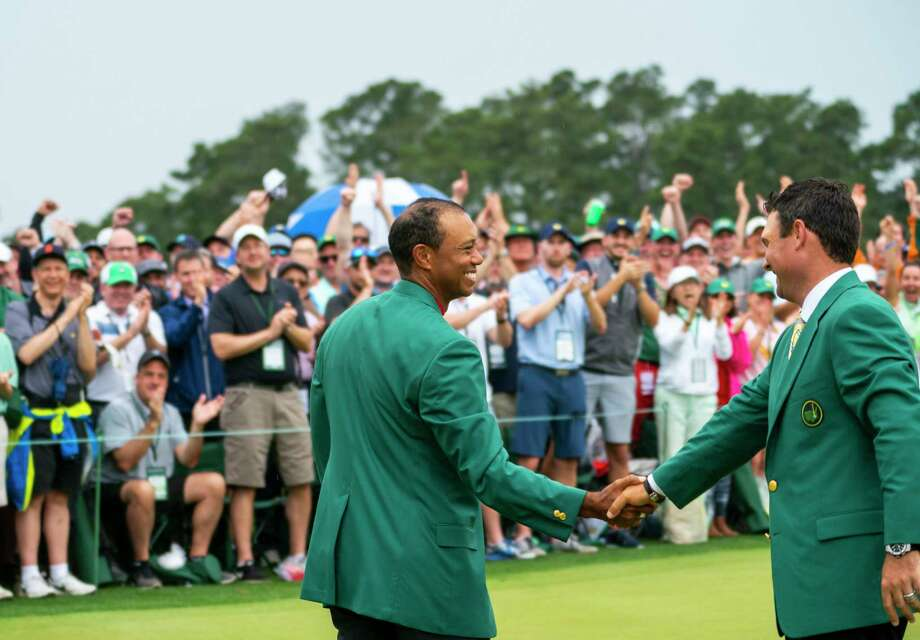 Tiger Woods shakes hands with Patrick Reed, last year's winner, in a ceremony after winning the Masters in Augusta, Ga., April 14, 2019. He captured his fifth Masters title and his 15th major tournament on Sunday, snapping a championship drought of nearly 11 years. (Doug Mills/The New York Times) Photo: DOUG MILLS / NYTNS