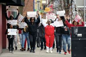 People march with signs toward Townsend Park for a rally to decry abuses by police on Sunday, April 14, 2019 in Albany, NY. (Phoebe Sheehan/Times Union)
