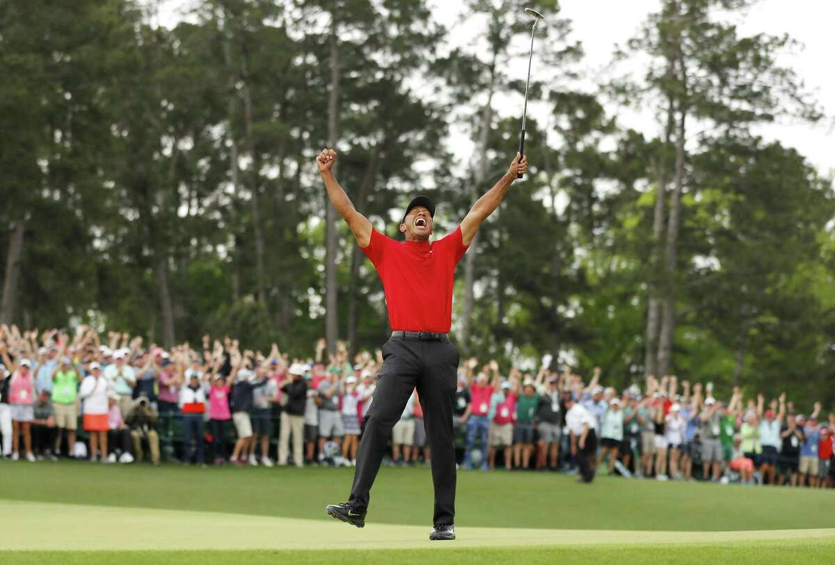 Tiger Woods celebrates after sinking his putt on No. 18 to win the Masters, his 15th major championship but first since 2008.
