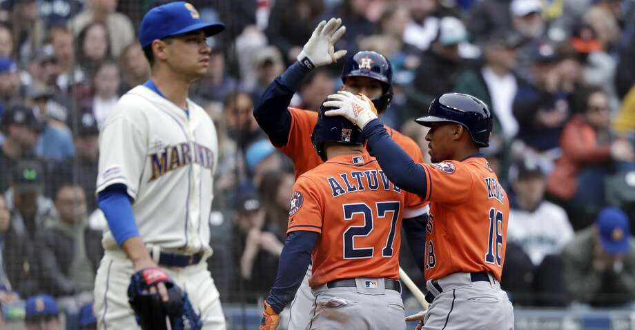Seattle Mariners starting pitcher Marco Gonzales, left, heads back to the mound as Houston Astros' Jose Altuve (27) and Tony Kemp (18) celebrate scoring with Carlos Correa in the sixth inning of a baseball game Sunday, April 14, 2019, in Seattle. (AP Photo/Elaine Thompson) Photo: Elaine Thompson/Associated Press