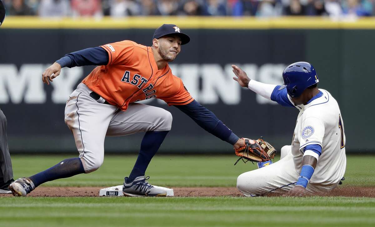 Seattle Mariners' Tim Beckham, right, slides into the tag of Houston Astros shortstop Carlos Correa as Beckham is thrown out on an attempted steal of second base in the second inning of a baseball game Sunday, April 14, 2019, in Seattle. (AP Photo/Elaine Thompson)