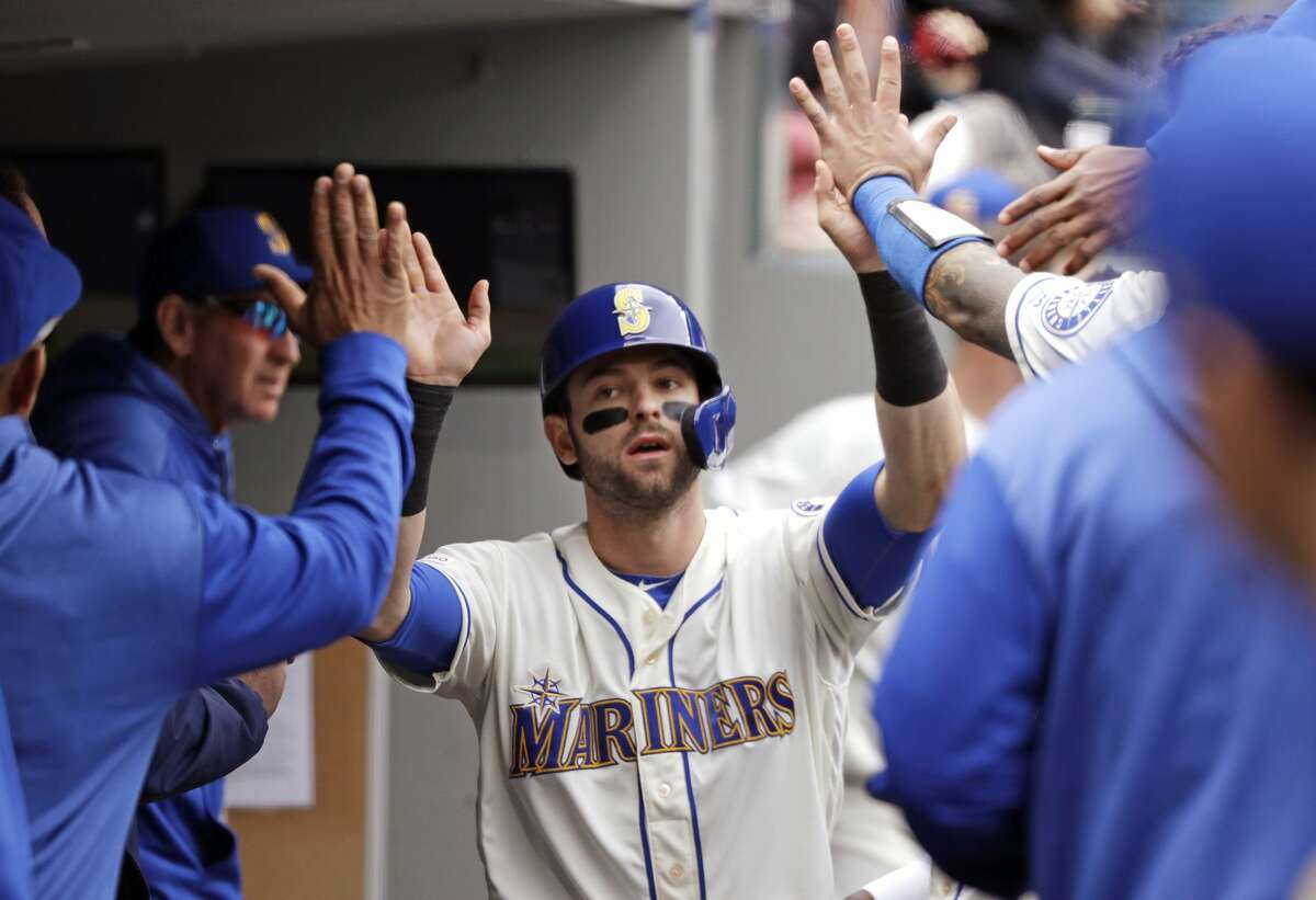 Seattle Mariners' Mitch Haniger is congratulated after scoring against the Houston Astros in the third inning of a baseball game Sunday, April 14, 2019, in Seattle. (AP Photo/Elaine Thompson)