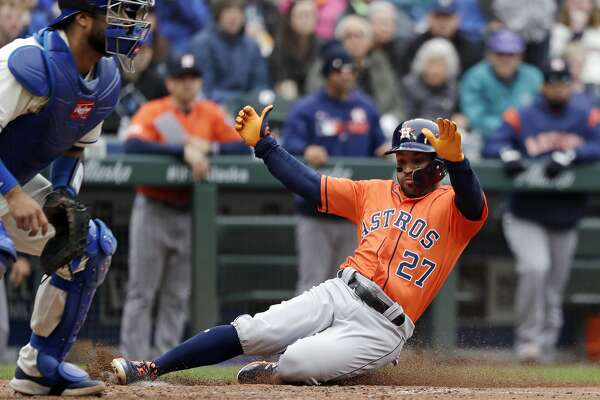 Houston Astros' Jose Altuve (27) scores as Seattle Mariners catcher Omar Narvaez waits for the ball in the sixth inning of a baseball game Sunday, April 14, 2019, in Seattle. (AP Photo/Elaine Thompson)