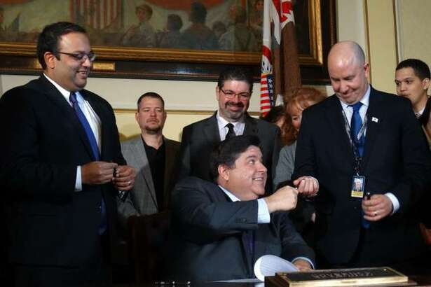 Gov. J.B. Pritzker hands a pen to Rep. Lance Yednock (D-Ottawa) after signing a bill that prohibits local governments in Illinois from enacting right-to-work ordinances. Also at the bill signing ceremony Friday in Springfield was Sen. Ram Villivalam (left), a Chicago Democrat who was lead sponsor of the bill in the Senate.