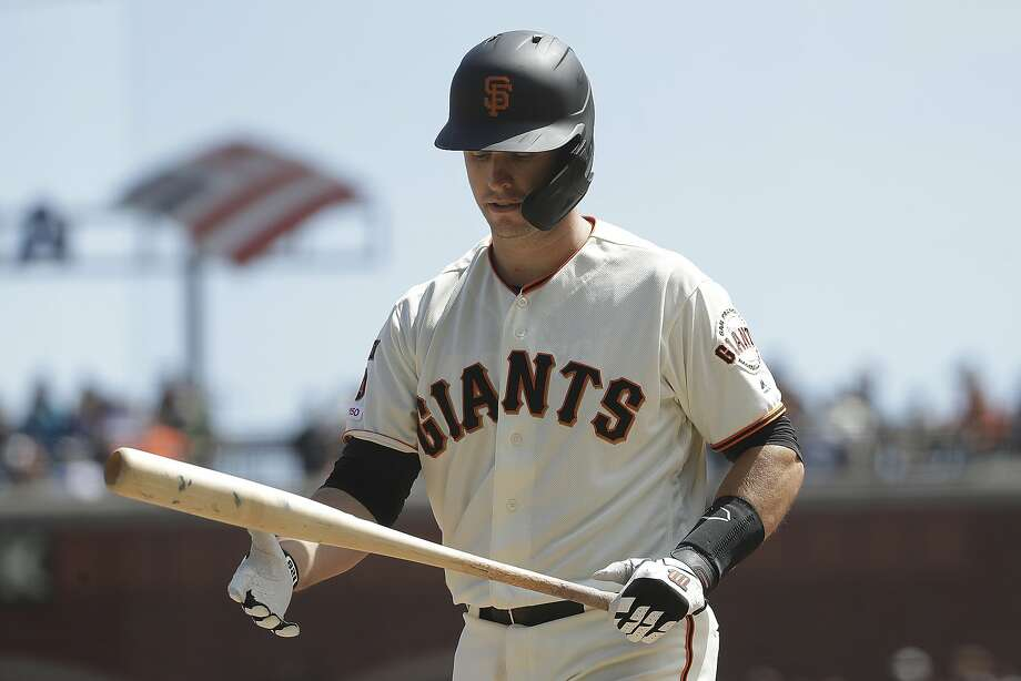 Giants catcher Buster Posey walks back after striking out in the fourth inning. Photo: Jeff Chiu / Associated Press