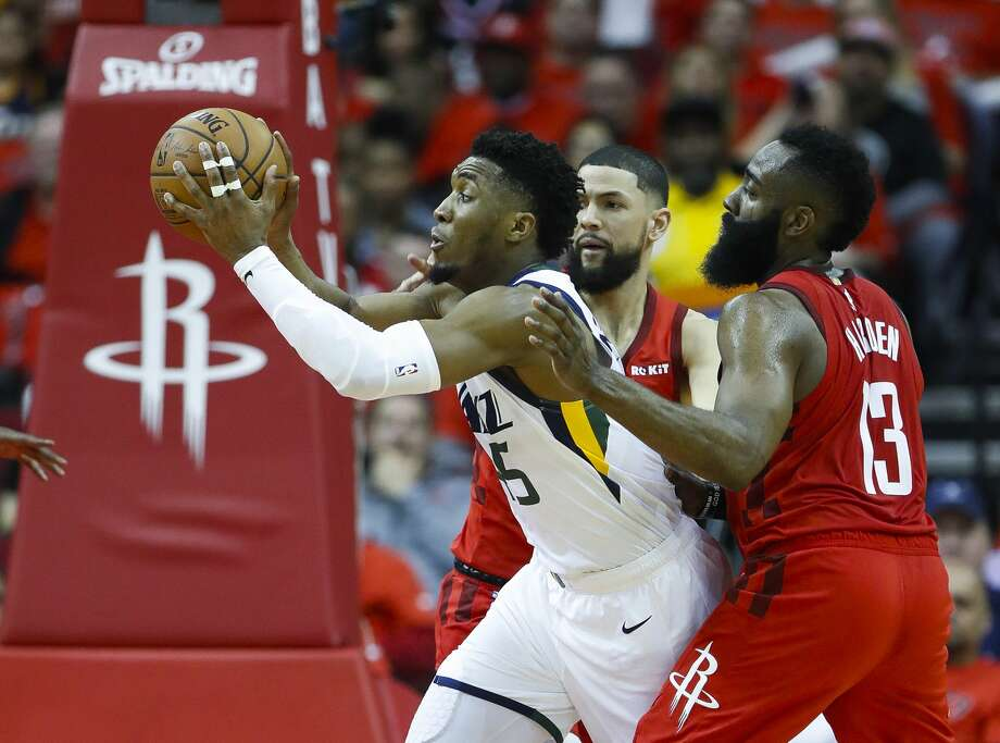 Utah Jazz guard Donovan Mitchell (45) drives between Houston Rockets guard James Harden (13) and guard Austin Rivers (25) during the second half of the first round of the NBA playoffs at Toyota Center, Sunday, April 14, 2019, in Houston. Photo: Karen Warren/Staff Photographer