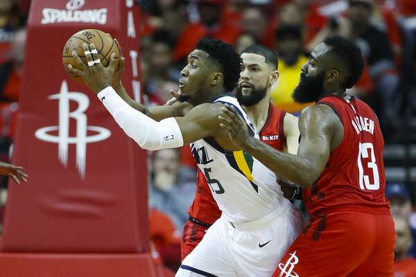 Utah Jazz guard Donovan Mitchell (45) drives between Houston Rockets guard James Harden (13) and guard Austin Rivers (25) during the second half of the first round of the NBA playoffs at Toyota Center, Sunday, April 14, 2019, in Houston.