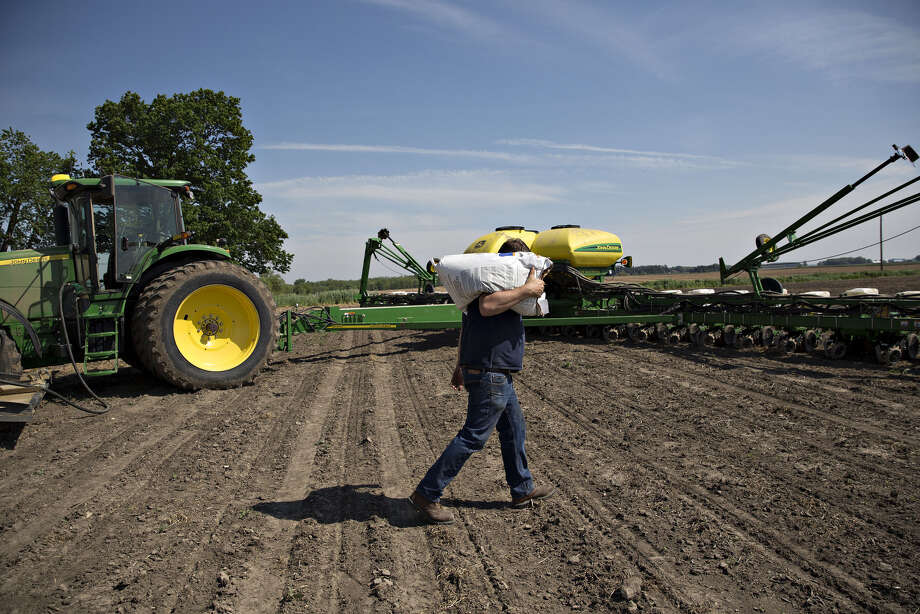 A farmer carries a bag of corn seed in Malden, Ill., on May 16, 2017. Photo: Bloomberg Photo By Daniel Acker. / © 2017 Bloomberg Finance LP