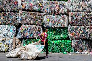 A worker walks in front of packed recyclable plastic bottles at La Sylvia recycling center in Barva, Costa Rica on June 20, 2018. Costa Rica discards 564 tons of plastic per day of which only 14 are recycled, according to the Ministry of Health's Office of Environmental Health.